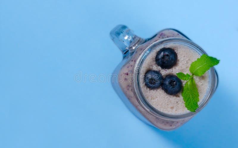 蓝莓圆滑的人用在金属螺盖玻璃瓶glas的薄菏用莓果和薄菏 在蓝色桌上的看法上 库存图片