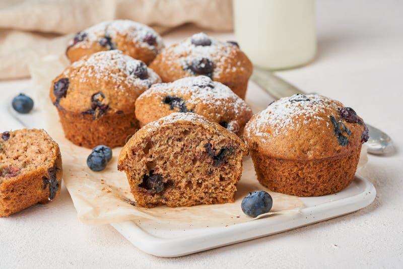 蓝莓松饼,侧视图,关闭 杯形蛋糕区分用在白色具体桌上的莓果 免版税库存图片