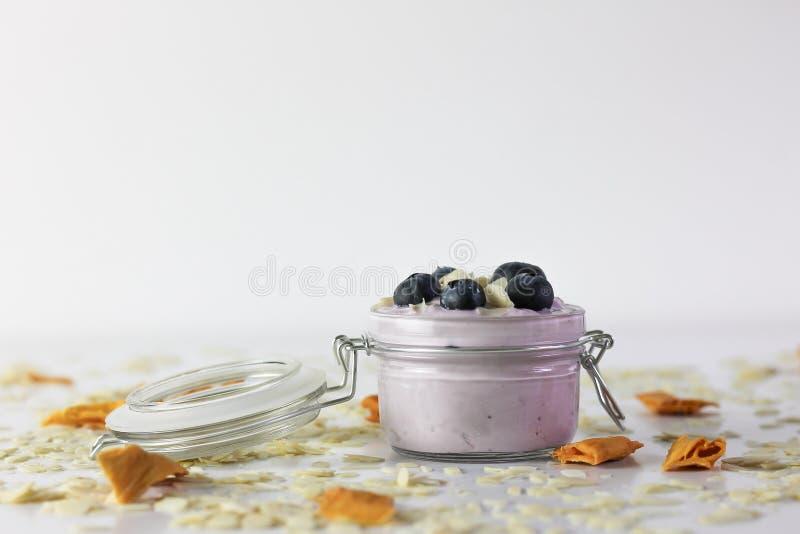 蓝莓酸奶照片,用蔓越桔和杏仁在黑板岩有白色背景 免版税库存照片
