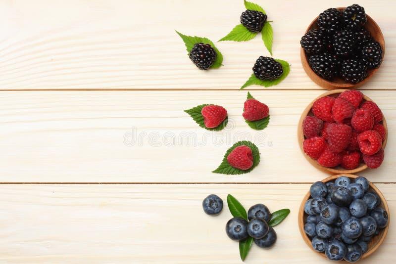 蓝莓,黑莓,在木碗的莓的混合在轻的木桌背景 与拷贝空间的顶视图 免版税库存图片