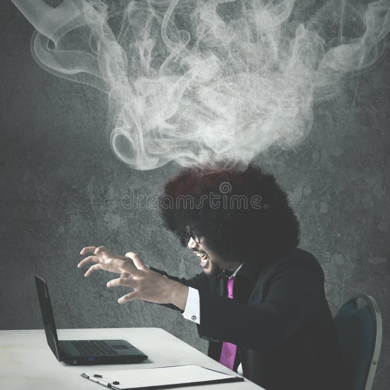 蓬松卷发商人恼怒与他残破的膝上型计算机 免版税库存照片