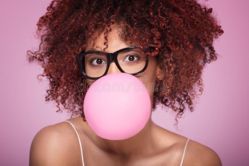 蓬松卷发女孩吹的泡泡糖气球 免版税图库摄影