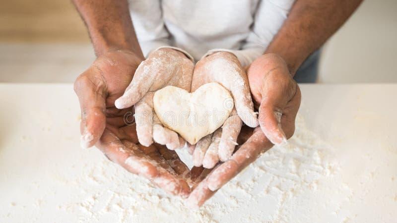 蓬松卷发握儿童手用心形的酥皮点心的人手 免版税图库摄影