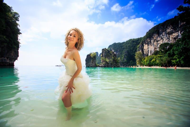蓬松礼服的白肤金发的新娘在浅天蓝色的海站立 库存图片
