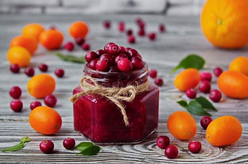 蔓越桔果酱和新鲜的蔓越桔在一个玻璃瓶子在一张灰色桌上 免版税库存图片