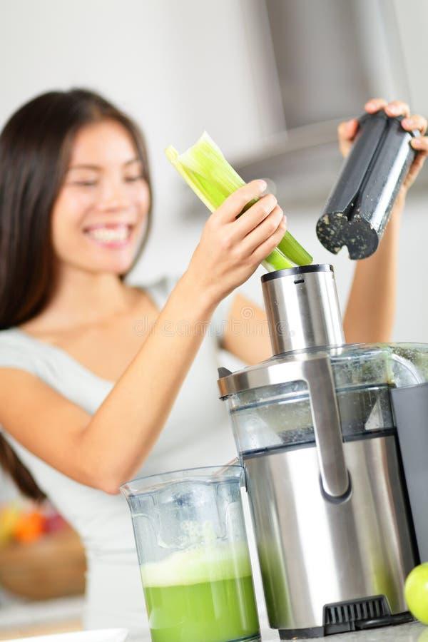 蔬菜汁- juicing绿色菜的妇女 图库摄影