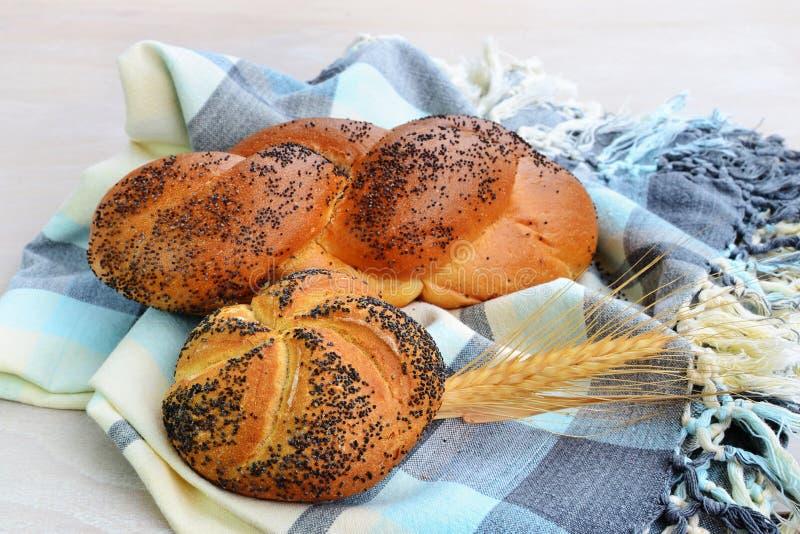 蔷薇花状小面包和Mohnflesserl把小圆面包编成辫子洒与罂粟种子 库存图片