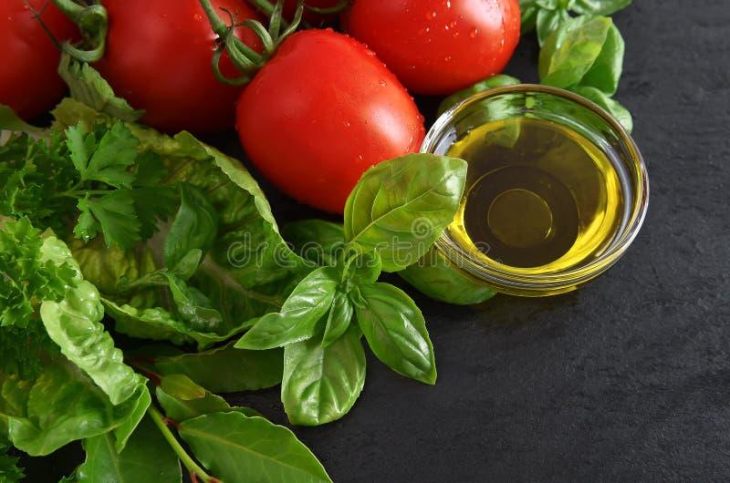 蕃茄、新鲜的蓬蒿叶子和橄榄油 健康的食物 库存照片
