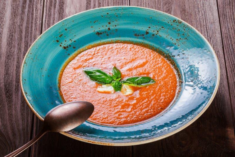蕃茄与蓬蒿、希腊白软干酪、冰和面包的gazpacho汤在黑暗的木背景,西班牙烹调 在桌上的成份 库存图片