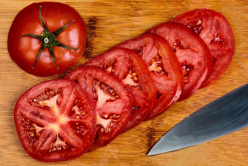 蕃茄切片的生动的图象的关闭在一个竹切板的 免版税库存图片