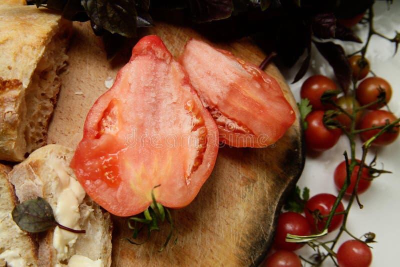 蕃茄和面包在委员会 免版税库存照片