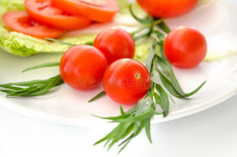 蕃茄和绿色在白色背景离开 图库摄影