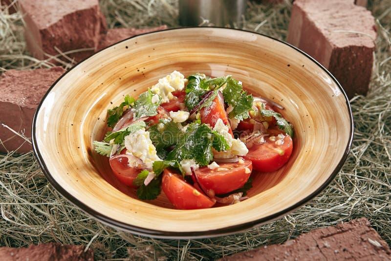 蕃茄沙拉用在土气样式干草背景关闭的红洋葱 免版税图库摄影