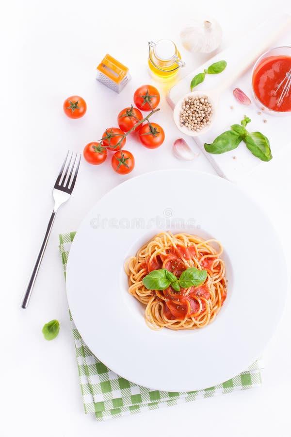 蕃茄面团意粉用新鲜的蕃茄、蓬蒿、意大利草本和橄榄油在一个白色碗在白色木背景 库存照片
