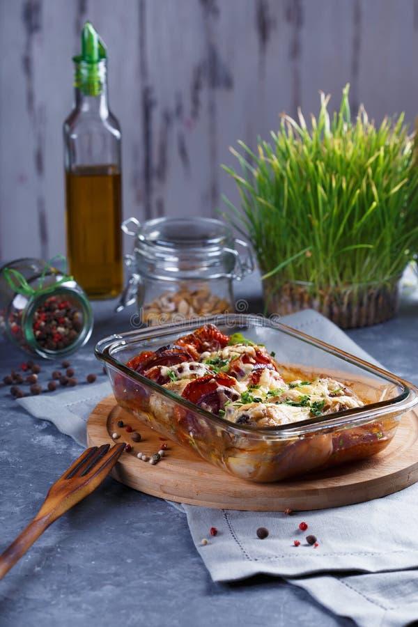 蕃茄鸡肉沙锅菜、葱、乳酪和香料菜单和餐馆概念在灰色背景在厨房用桌上与 库存照片