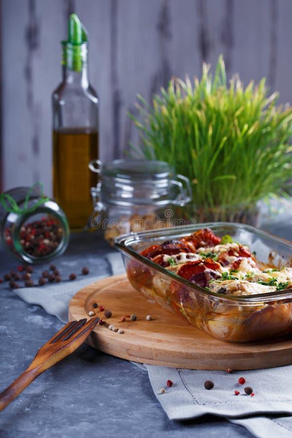蕃茄鸡肉沙锅菜、葱、乳酪和香料菜单和餐馆概念在灰色背景在厨房用桌上与 免版税图库摄影