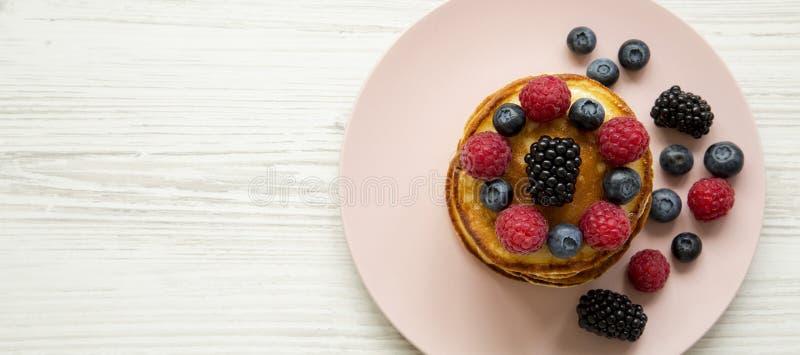 薄煎饼用在一块桃红色板材的莓果在白色木背景,顶视图 r r 库存照片