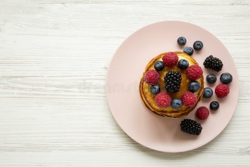 薄煎饼用在一块桃红色板材的莓果在白色木表面,顶视图 库存照片
