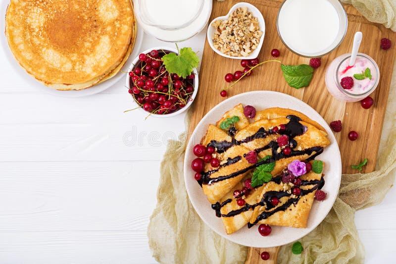 薄煎饼用巧克力、蜂蜜、坚果和夏天莓果 库存照片