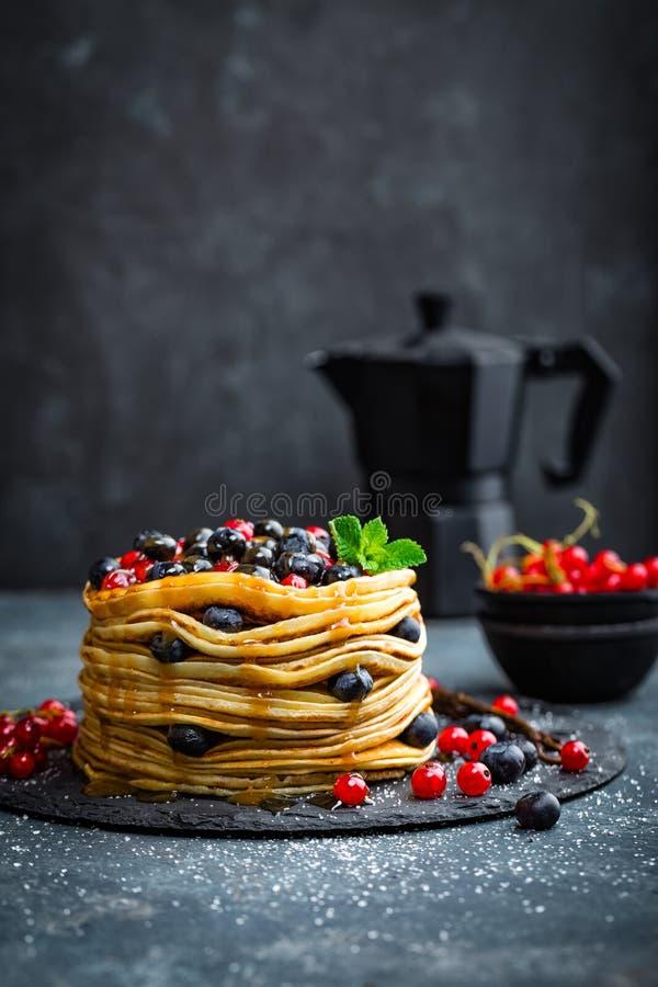 薄煎饼用新鲜的莓果和枫蜜在黑暗的背景 免版税图库摄影