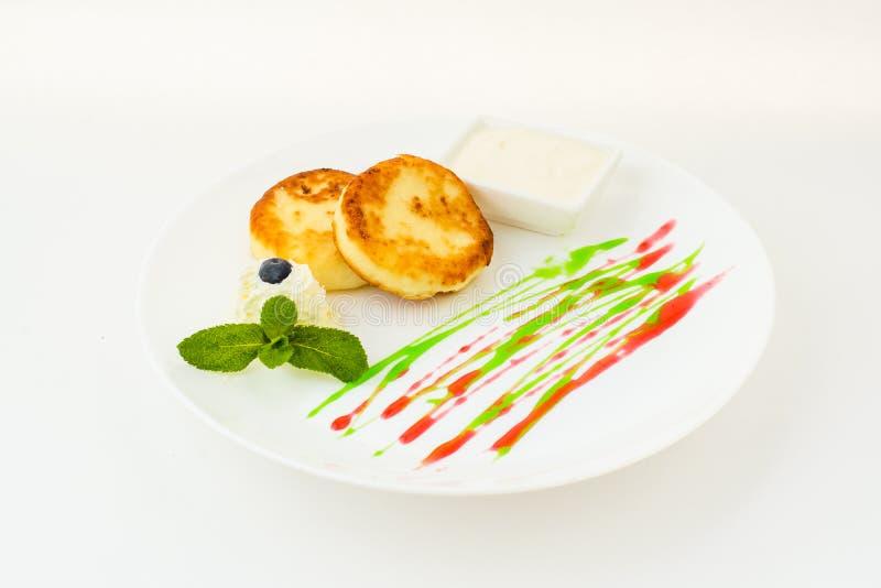 薄煎饼用果酱和薄菏在白色隔绝的板材 图库摄影