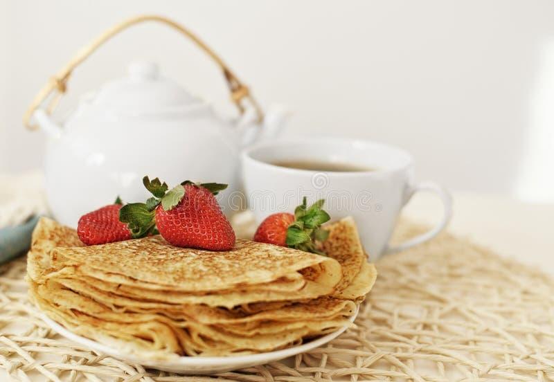 薄煎饼用草莓和热的茶在茶壶和杯子 免版税图库摄影