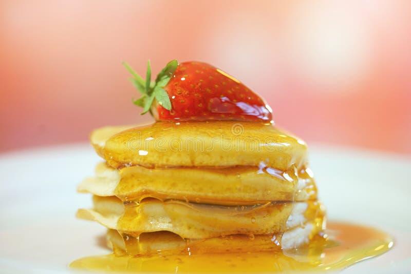 薄煎饼用草莓在上面和下毛毛雨用糖浆,宏观特写镜头 免版税库存图片