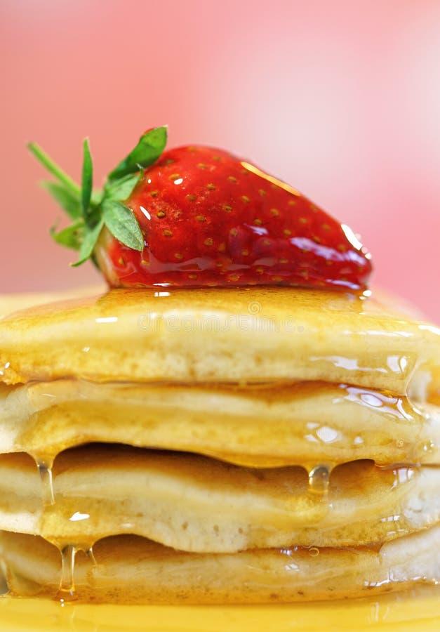 薄煎饼用草莓在上面和下毛毛雨用糖浆,宏观特写镜头 库存图片