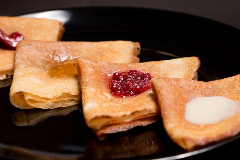 薄煎饼用草莓酱、山莓果酱、酸性稀奶油和蜂蜜 免版税库存图片