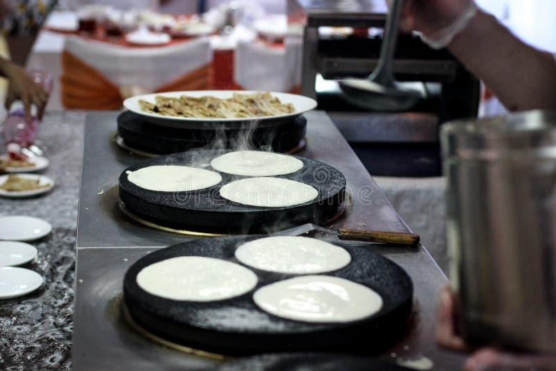 薄煎饼,烘烤的薄煎饼,厨师在餐馆准备,早餐,厨师油煎在板材,烹调PR的薄煎饼 免版税库存图片