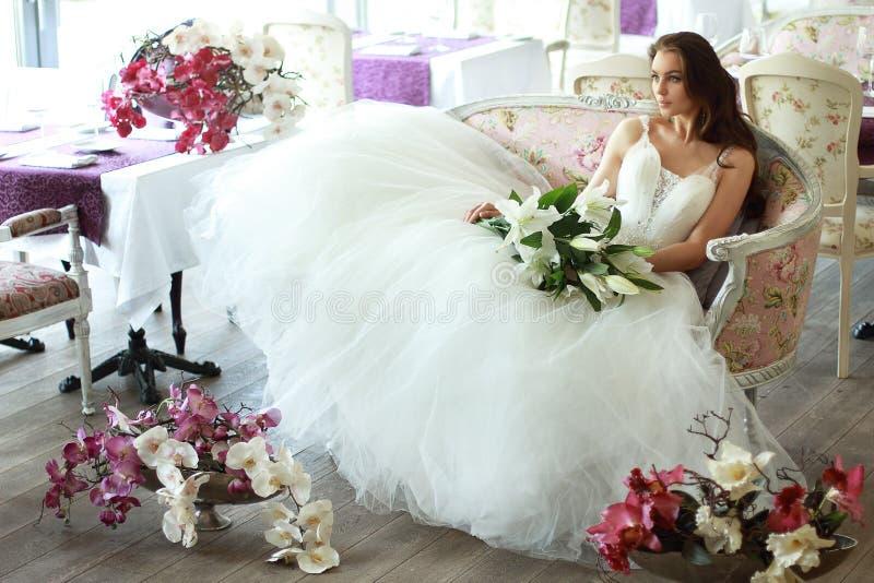 薄纱一套壮观的白色婚礼礼服的美丽的新娘有束腰的坐有花束百合和兰花的沙发 图库摄影