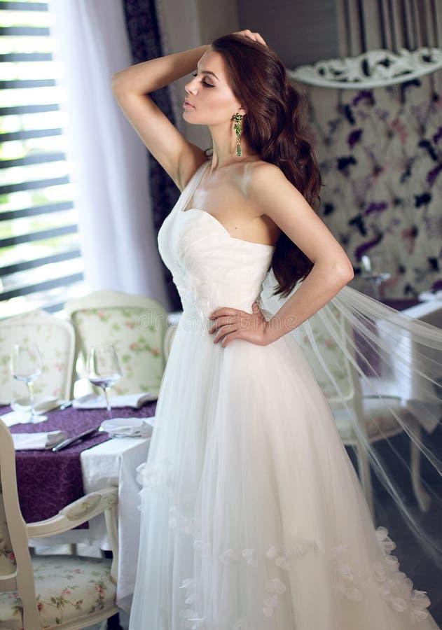 薄纱一套壮观的白色婚礼礼服的美丽的新娘有束腰的坐有花束百合和兰花的沙发 库存图片