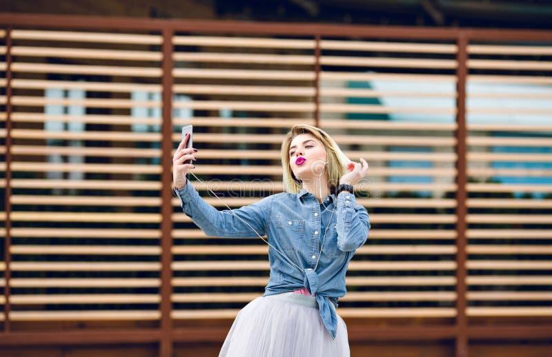 薄纱裙子和牛仔布衬衣的美丽的时髦的女孩有紫色嘴唇的获得乐趣并且做与亲吻面孔的selfie 免版税库存图片