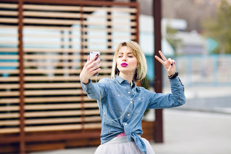 薄纱裙子和牛仔布衬衣的美丽的时髦的白肤金发的女孩有紫色嘴唇的获得乐趣并且做与亲吻的selfie 免版税库存照片