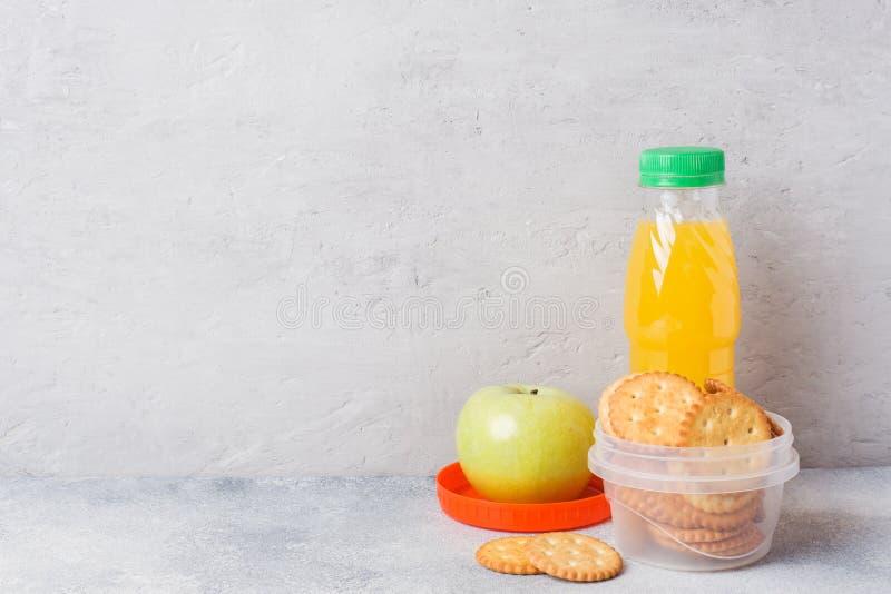 薄脆饼干和新鲜的苹果计算机和橙汁过去在灰色桌上 r 概念学校早餐 库存图片