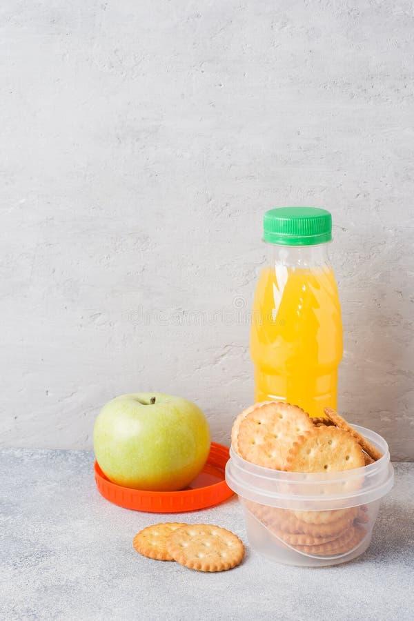 薄脆饼干和新鲜的苹果计算机和橙汁过去在灰色桌上 r 概念学校早餐 免版税库存图片