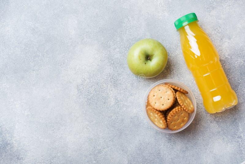 薄脆饼干和新鲜的苹果计算机和橙汁过去在灰色桌上 r 概念学校早餐 库存照片