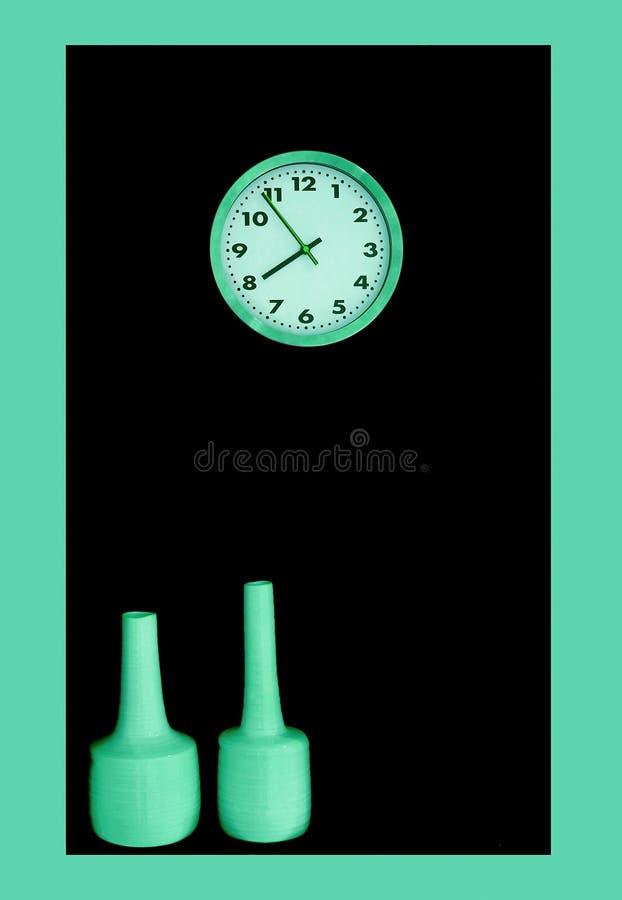 薄荷的绿色时钟和花瓶在装饰空间的黑色墙壁上 免版税库存图片