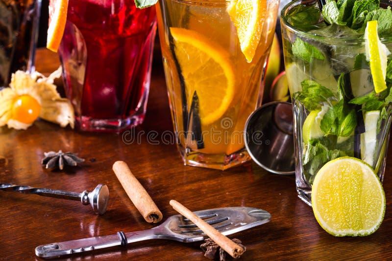 薄荷的mojito鸡尾酒,橙色鸡尾酒,在玻璃玻璃的草莓鸡尾酒与秸杆 酒吧辅助部件:振动器 库存图片