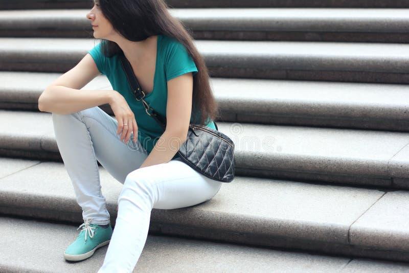 薄荷的T恤杉和白色牛仔裤的少妇有现代皮革的 免版税库存图片