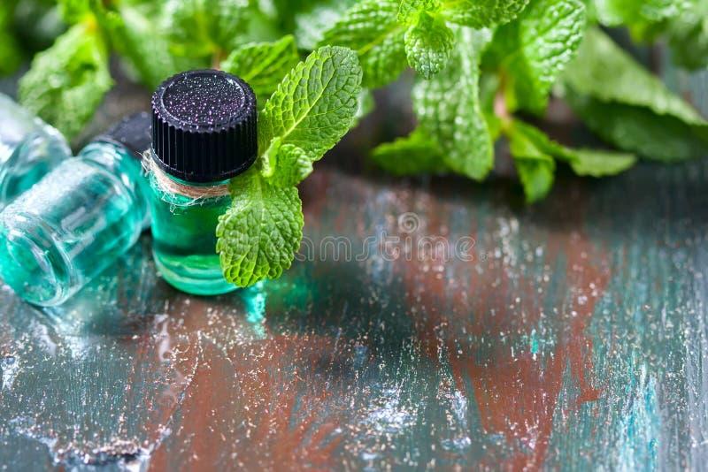 薄荷,在木背景的新鲜的绿色薄菏的精油在小瓶的 免版税库存图片