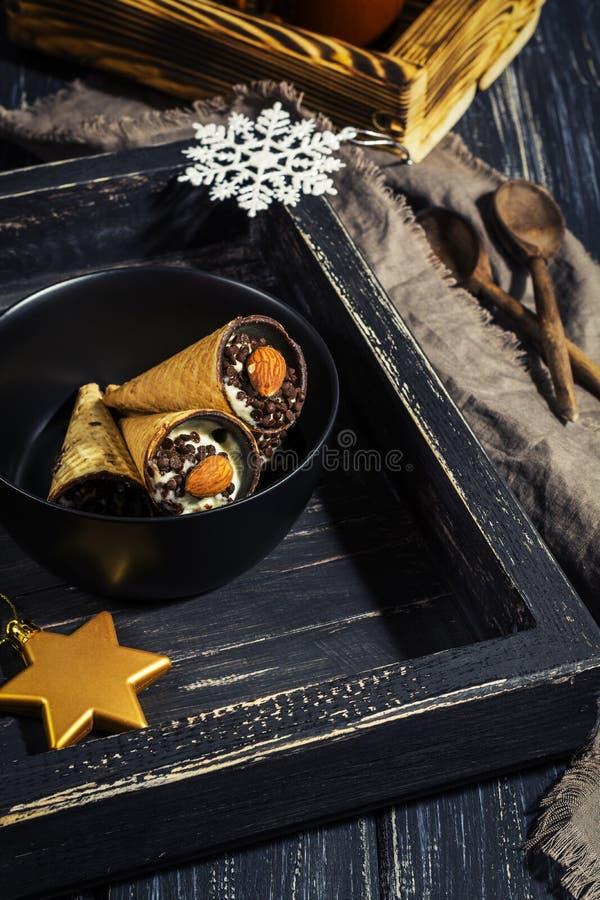 薄酥饼杯子用酸奶干酪和巧克力在一个老黑木盘子 选择聚焦 库存照片
