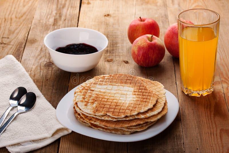 薄酥饼,果酱,苹果,在一张木桌上的橙汁立场 免版税库存图片