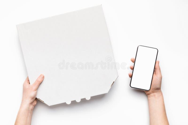 薄饼交付 拿着纸板箱和电话的传讯者 免版税库存图片