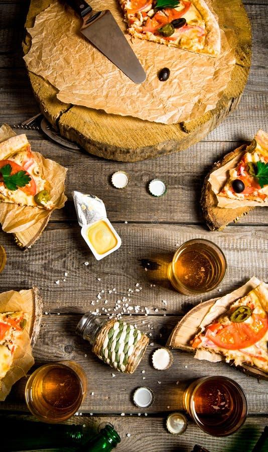 薄饼和啤酒四个人的 在一张木表 库存图片