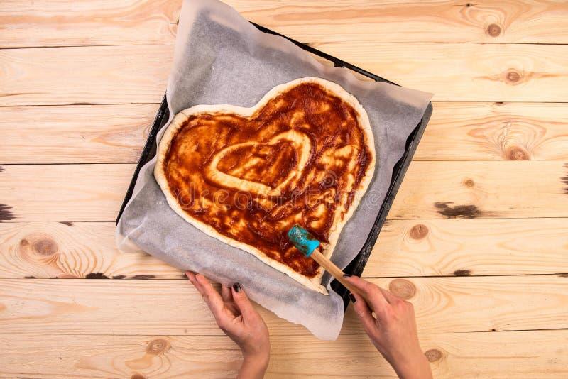 薄饼心脏爱华伦泰` s天浪漫意大利餐馆晚餐食物 熏火腿,橄榄,蕃茄,荷兰芹,蓬蒿 图库摄影