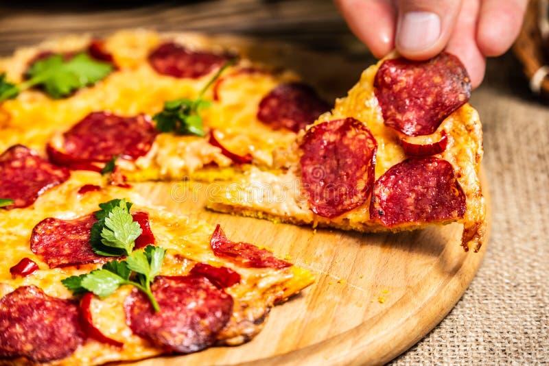 薄饼用乳酪和蒜味咸腊肠在手中在一块木板材 免版税图库摄影