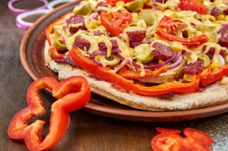 薄饼用蒜味咸腊肠、蕃茄、甜椒、洋葱圈、绿橄榄、玉米、乳酪和香料在一块黑暗的板材 免版税图库摄影