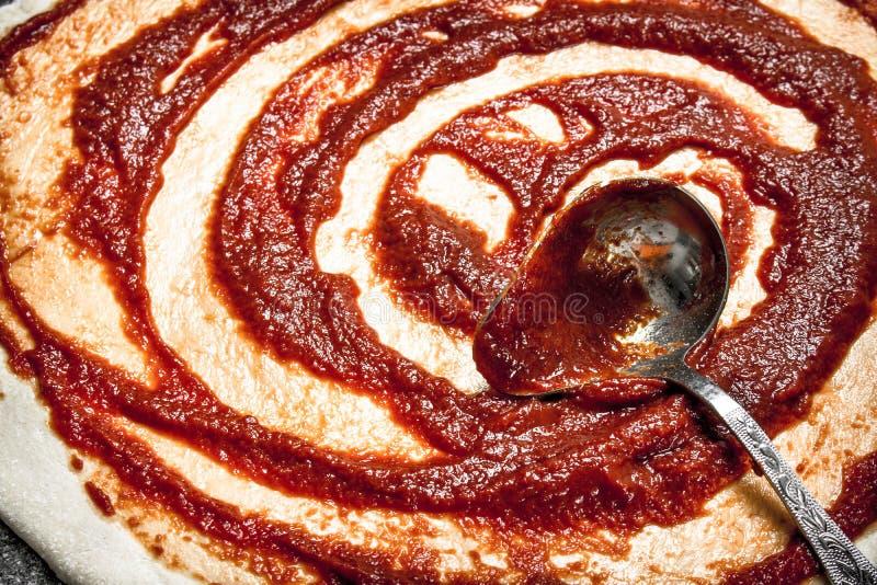 薄饼的准备 西红柿酱的应用在滚动的面团的 免版税库存照片