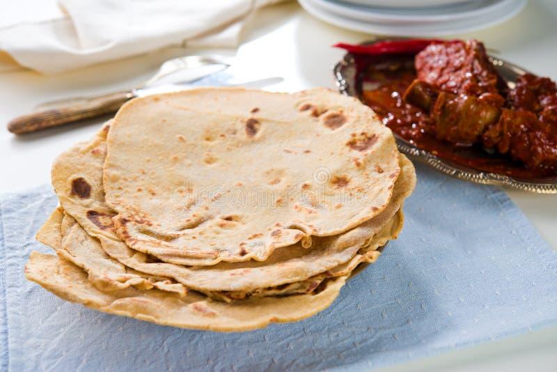 薄饼roti和印地安食物在餐桌上。 免版税库存图片